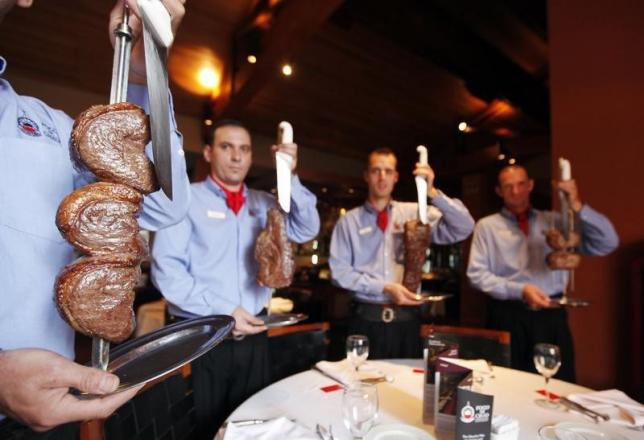 Waiters hold skewers of meat at the Fogo de Chao Brazilian steakhouse, where food is prepared in the traditional gaucho way, in Sao Paulo April 15, 2014. REUTERS/Paulo Whitaker